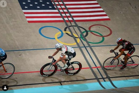 photo of bikers on a velodrome with the American Flag and Olympic Rings